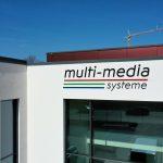 Logo über dem Eingang des Neubaus der multi-media systeme AG